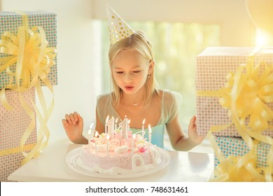 little birthday girl blowing blow out candles on cake and making a wish.