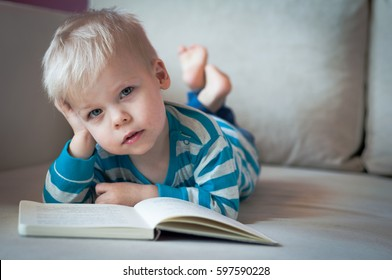 Little, a bit sad, pensive, two years old boy lying on his belly on the sofa, with open book in front of him, looking at camera.