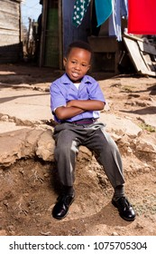 Little black boy with a cute smile sitting down in a township wearing his school uniform.