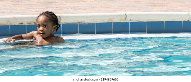Little black boy relaxing poolside