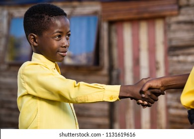 Little black boy shaking hands with his friend while wearing school clothes.