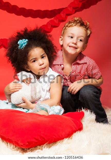 Little black curly dark girl and Caucasian blond boy hugging