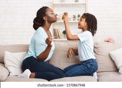 Little Black Daughter Doing Makeup For Her Mother Sitting On The Couch At Home, Having Fun