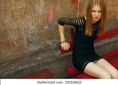 Little black dress concept. Portrait of beautiful fashionable woman in black cocktail dress sitting on red bench in old italian yard. Drawings on wall. Vintage style. Copy-space. Outdoor shot