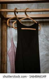 Little black dress hanging on a  clothing rack, rappan wooden hangers. Boho chic style. Fashion blogging concept, neutral colors. Loft bedroom interior design