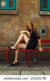 Little black dress and high heels concept. Portrait of a beautiful fashionable woman in black cocktail dress and high heel shoes sitting in old italian yard. Bright colors. Vogue style. Outdoor shot