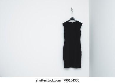 Little black dress on a hanger in front of a white wall. Female formal style look.