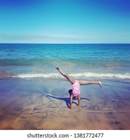 Little black girl doing cartwheels on the beach.