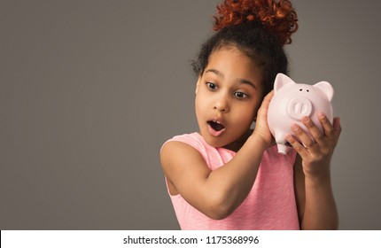Little black girl with piggy bank, studio shot, copy space