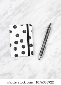 Little black and white diary and pen on marble background.