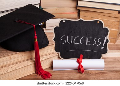 "Little blackboard that reads ""Success!"" next to a diploma, some books, and a black mortarboard with red tassel."