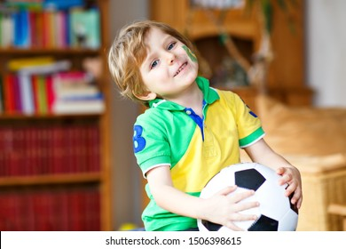 Little blond adorable kid boy with ball watching soccer football cup game on tv. Funny happy crying child fan having fun and cheering winning football team. Champions and world cup concept