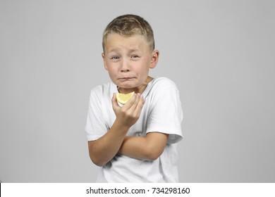 Little, blond boy biting into a lemon and make a face