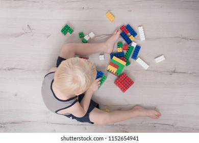 Little blond boy is building of colored designer. Top view