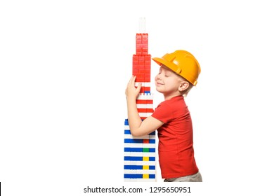 Little blond boy in the construction helmet and a red shirt stands and hugs tower built from parts designer. Portrait. Isolate on white background