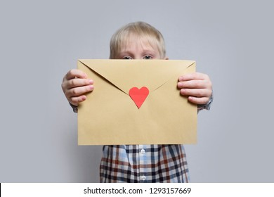 Little blond boy holds an envelope with heart on light background