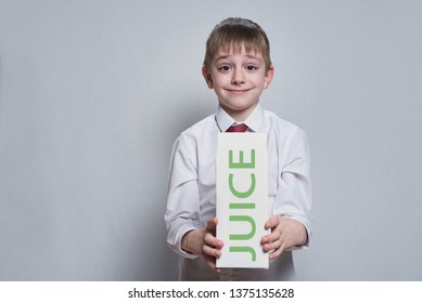little blond boy holds and shows a big white carton juce package. White shirt and red tie. Light background.