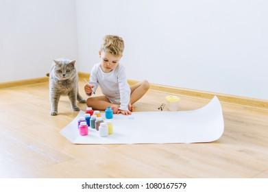 a little blond boy paints a paper with a cat