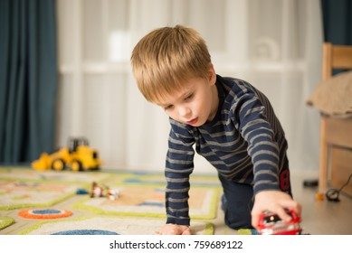 Little blond boy playing with cars and toys at home, indoor
