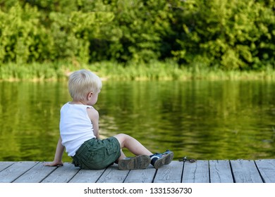 Little blond boy sitting on a pier on the bank of the river amid a green forest.