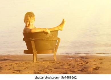 Little blond boy sitting in rusty pot on the beach in the sunlight