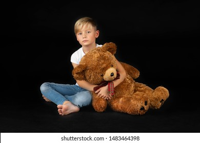 little blond boy is sitting sadly on the floor with a big teddy