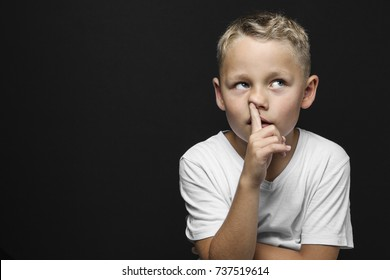 little blond boy thinks and drills with the pointing finger in the nose