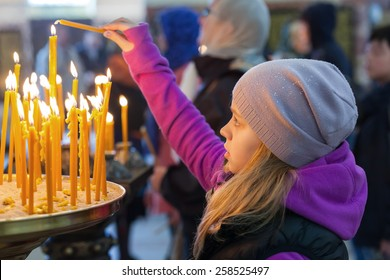 Little blond Caucasian girl with candles in Orthodox Church