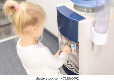 Little  blond caucasian girl getting water from a cooler in a school or kindergarten.
