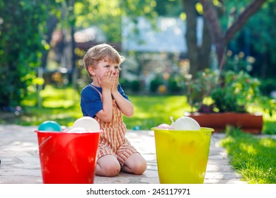 Little blond child boy having fun with splashing water in summer garden. Kid making water bombs and playing with family. Outdoor leisure with kids on hot summer day.