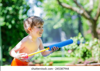 Little blond child having fun with splashing water in summer garden, playing water gun. Outdoors leisure with kids in summer, on sunny hot day.