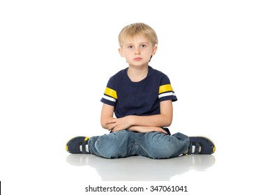 Little blond cute boy sitting on the floor and sad. Isolated on white background. Shooting in the studio