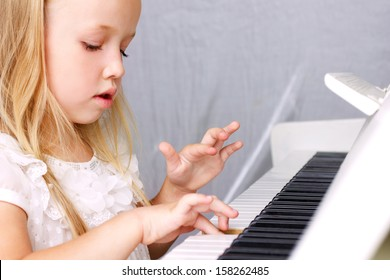 little blond girl in beautiful white dress playing on white piano, closeup