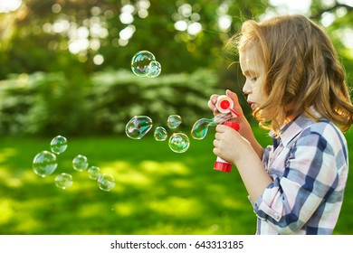 A little blond girl blows soap bubbles in a park