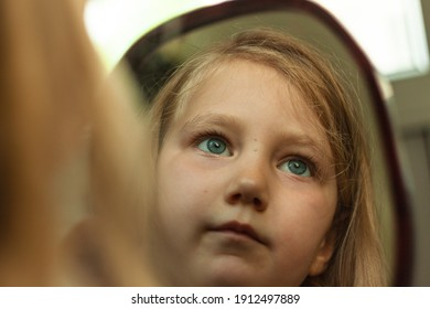 Little blond girl with blue eyes looking in the mirror. Cute serious curious child admires herself in reflection. Kids home portrait in daylight near window. Growing up psychology personal development