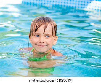Little blond girl with blue eyes enjoys swimming in a pool outdoors