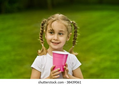 Little Blond Girl with braids holding pink cup