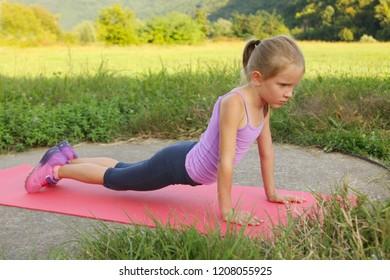 Little blond girl doing fitness yoga exercises plank in the park