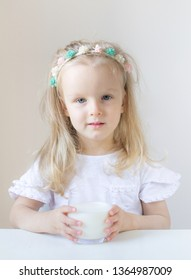 Little blond girl drink a glass of milk with different emotions, indoor, healthy food concept
