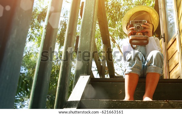 Little blond girl enjoying summer vacation time at the tree house. Gardening