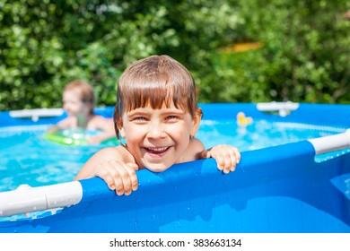 Little blond girl enjoying summertime  in a pool