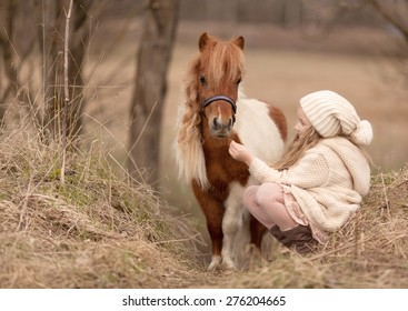 little blond girl with long hair in cream hat and coat is sitting near the little horse and feed her