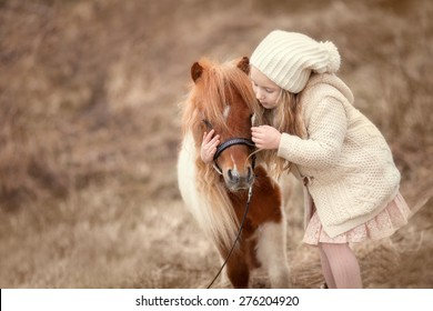 little blond girl with long hair in cream hat and coat is standing near the little horse pony and hugging it
