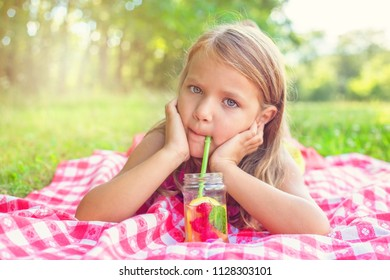 Little blond girl lying on the grass and sipping lemonade