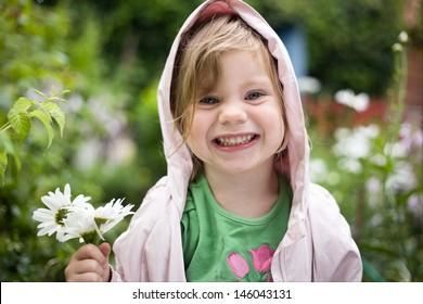 little blond girl model in the green garden. Summer