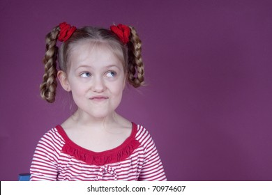 Little blond girl with pig tails making silly faces