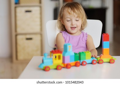 Little blond girl  playing with  colorful plastic blocks indoor.