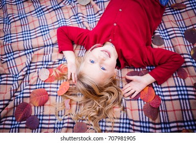 Little blond girl in red is lying on the ground in the fallen leaves. Autumn forest picnic. Halloween holiday.