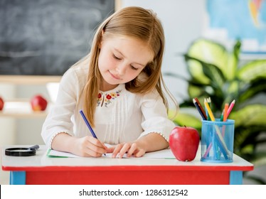 Little blond girl sitting at the white desk and writing classwork in the copybook in the school classroom