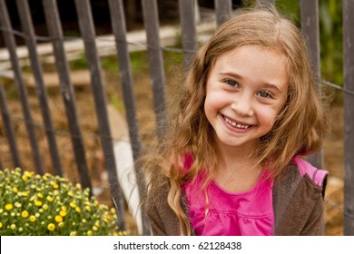 Little Blond Girl Smiling Next To Yellow Mums